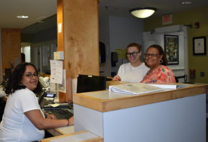 in medical clinic setting, three women pose behind a counter